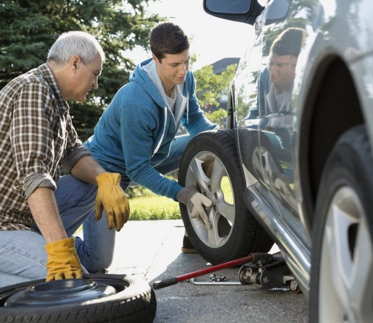 Father and son changing car tire