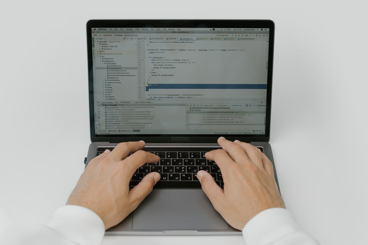 person writing code on laptop
